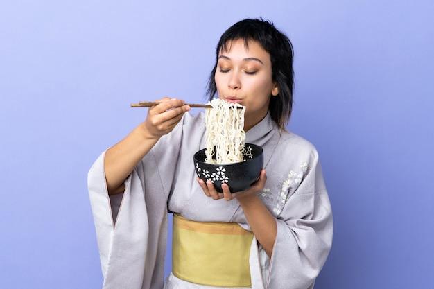 Jonge vrouw die kimono over geïsoleerde blauwe achtergrond draagt die een kom van noedels met eetstokjezand houdt die het blaast omdat zij heet zijn