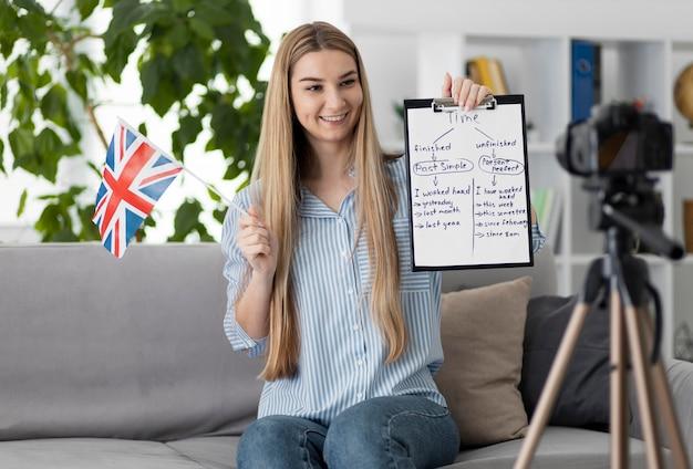 Jonge vrouw die kinderen in engelse klas online onderwijst