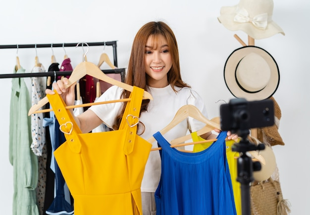 Jonge vrouw die kleding en accessoires online verkoopt via live streaming van smartphones, zakelijke online e-commerce thuis