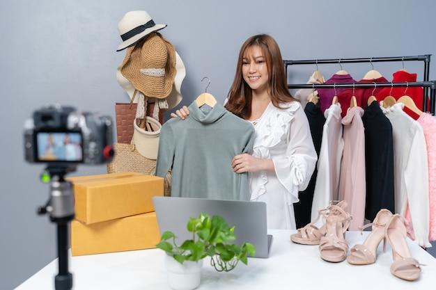 Jonge vrouw die kleding en accessoires online verkoopt via livestreaming van de camera, zakelijke online e-commerce thuis