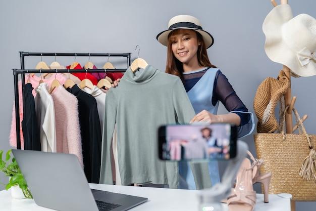 Jonge vrouw die kleding en hoed online verkoopt door smartphone live streaming, zakelijke online e-commerce thuis
