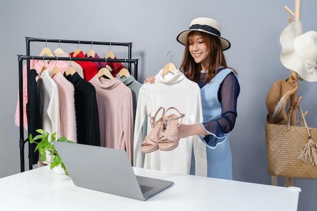 Jonge vrouw die kleding en toebehoren online verkoopt door laptop computer live streaming, zakelijke online e-commerce thuis