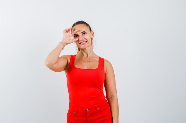 Jonge vrouw die klein formaat in rood mouwloos onderhemd, broek toont en verward, vooraanzicht kijkt.
