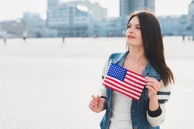 Jonge vrouw die kleine amerikaanse vlag houdt tijdens viering van de dag van de onafhankelijkheid
