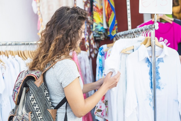 Jonge vrouw die kleren in de winkel kijkt