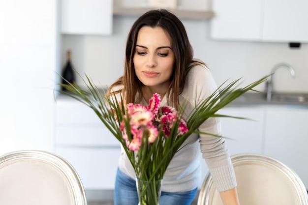 Jonge vrouw die kleurrijke bloemen in vaas ruikt
