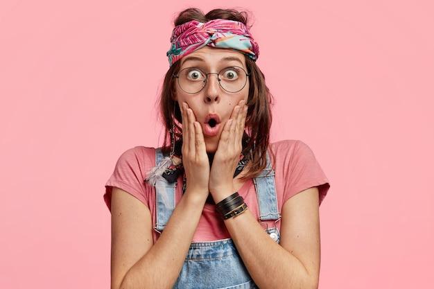Jonge vrouw die kleurrijke hoofdband en denimoveralls draagt