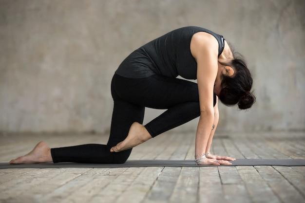 Jonge vrouw die knie aan voorhoofdkruloefening doet