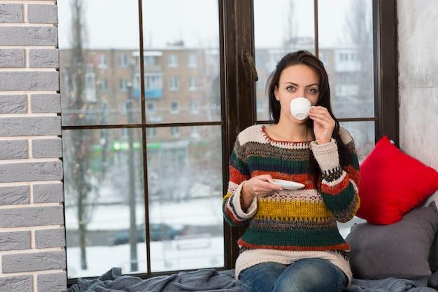 Jonge vrouw die koffie drinkt terwijl ze op de vensterbank zit met kussens en deken in de woonkamer