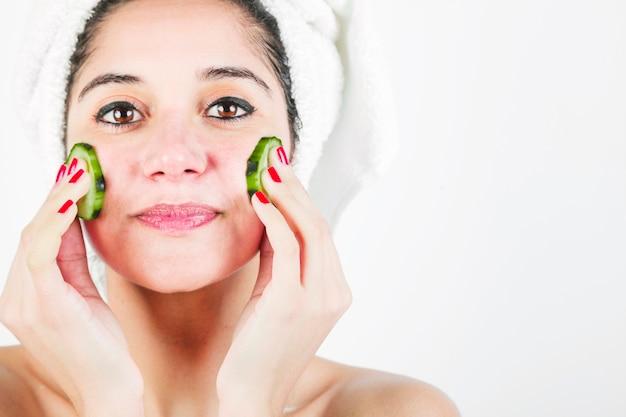 Jonge vrouw die komkommerplakken over haar kuikens tegen witte achtergrond toepast