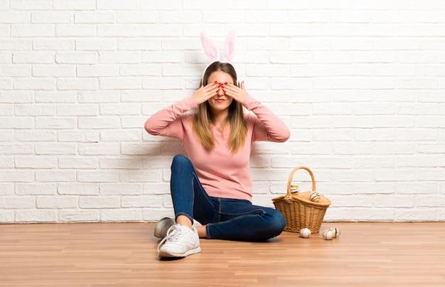 Jonge vrouw die konijntjesoren voor pasen-vakantie draagt die ogen behandelt door handen