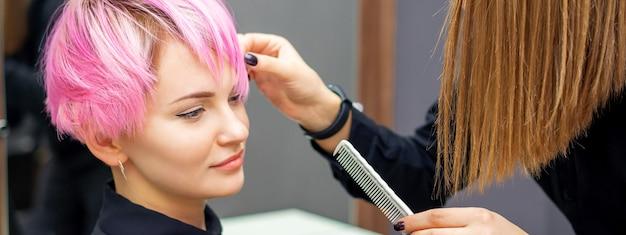 Jonge vrouw die kort roze kapsel krijgt