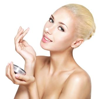 Jonge vrouw die kosmetische room op de geïsoleerde neus toepast -