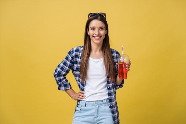 Jonge vrouw die koude drank vasthoudt en drinkt in vrijetijdskleding. mooi meisje glimlachend gelukkig lachen camera kijken.