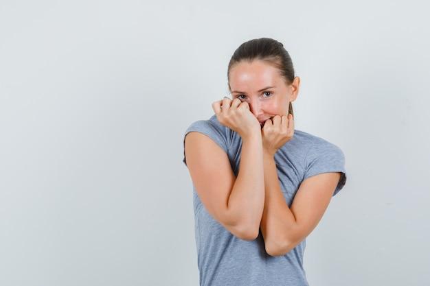 Jonge vrouw die kraag op gezicht in grijs t-shirt trekt en verlegen, vooraanzicht kijkt.
