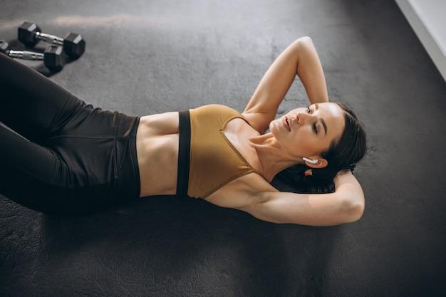 Jonge vrouw die kraken op vloer doen bij gymnastiek