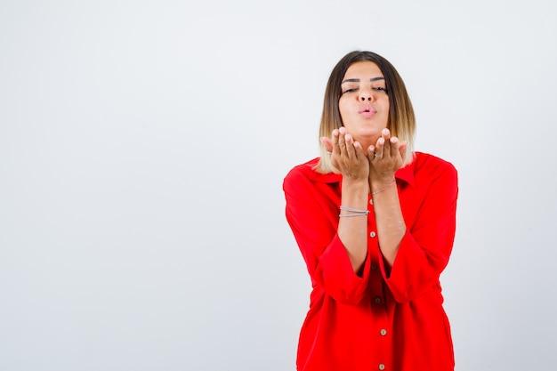 Jonge vrouw die kus verzendt met pruilende lippen in rood oversized shirt en er schattig uitziet, vooraanzicht.