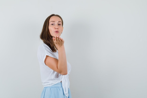 Jonge vrouw die kusjes naar voren in witte blouse en lichtblauwe rok verzendt en charmant kijkt