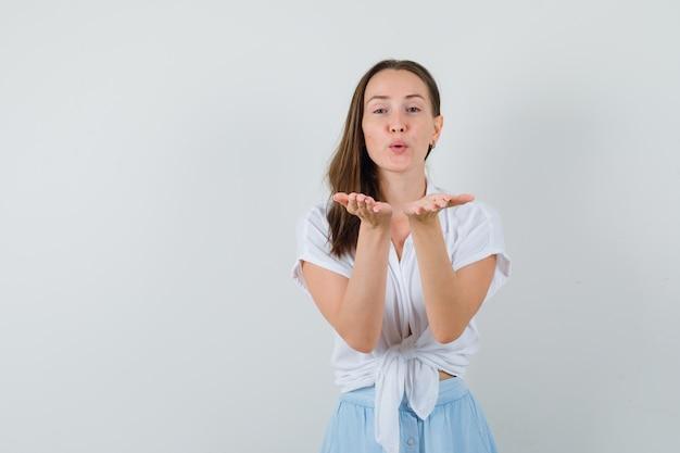 Jonge vrouw die kusjes naar voren in witte blouse en lichtblauwe rok verzendt en gelukkig kijkt
