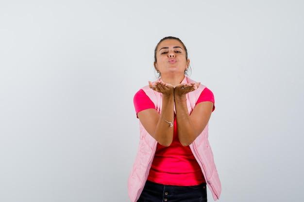 Jonge vrouw die kusjes stuurt in roze t-shirt en jasje en er mooi uitziet