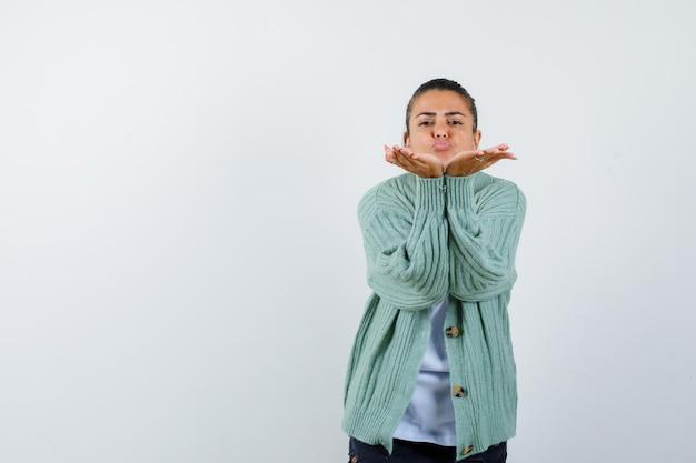 Jonge vrouw die kusjes stuurt in wit t-shirt en mintgroen vest en er aantrekkelijk uitziet