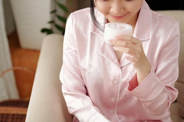 Jonge vrouw die lacht als ze nieuwe jongenslotion ruikt die ze gaat aanbrengen