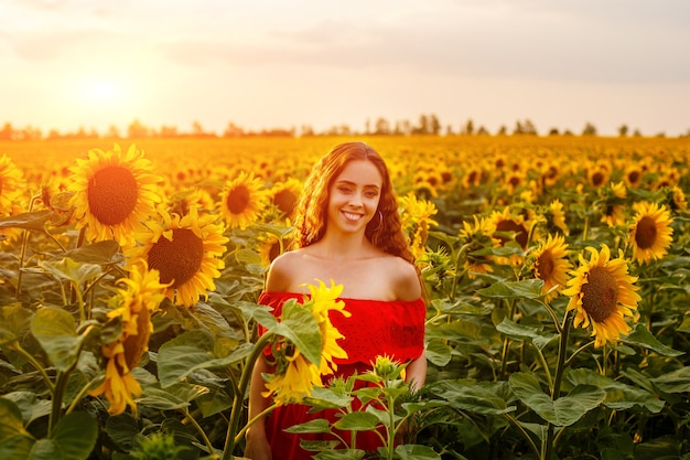 Jonge vrouw die lacht bij zonsondergang in een veld met zonnebloemen een schattig meisje met een kaukasisch uiterlijk in een rode ...