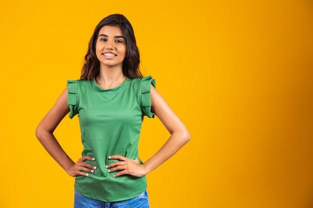 Jonge vrouw die lacht camera kijken op gele achtergrond.