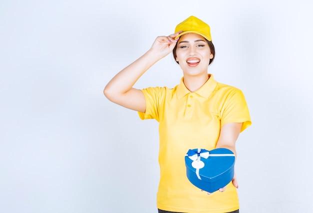 Jonge vrouw die lacht en een doos in de vorm van een hart vasthoudt