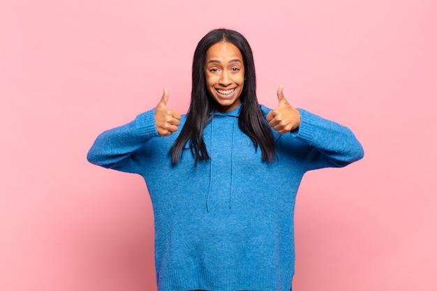 Jonge vrouw die lacht en er in het algemeen gelukkig, positief, zelfverzekerd en succesvol uitziet, met beide duimen omhoog