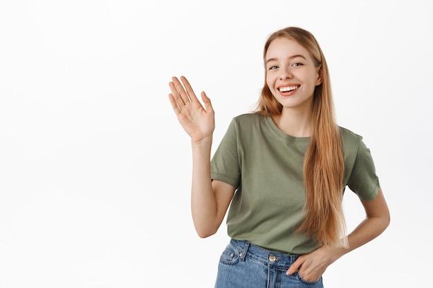 Jonge vrouw die lacht en hallo zegt, je groet, mensen verwelkomt, in zomerkleren tegen een witte muur staat