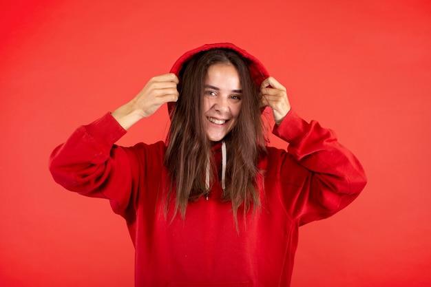 Jonge vrouw die lacht geïsoleerd op rood