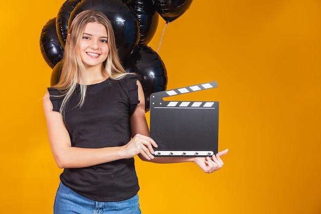 Jonge vrouw die lacht met klassieke zwarte film die klepelbord maakt en viert met zwarte luchtballonnen geïsoleerd op gele achtergrond. verjaardagsfeestje, mensen emoties concept.