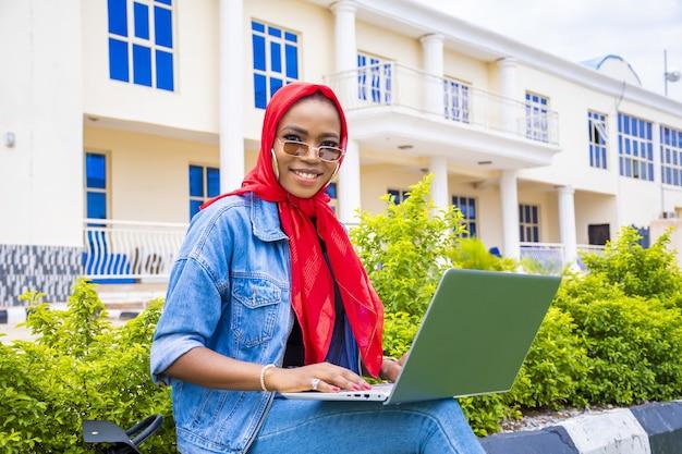 Jonge vrouw die lacht terwijl ze met haar laptop in een park zit