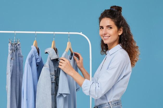 Jonge vrouw die lacht tijdens het kiezen van een spijkerbroek jasje op het rek in de winkel