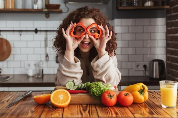 Jonge vrouw die lacht tijdens het koken van salade met verse groenten in het interieur van de keuken thuis