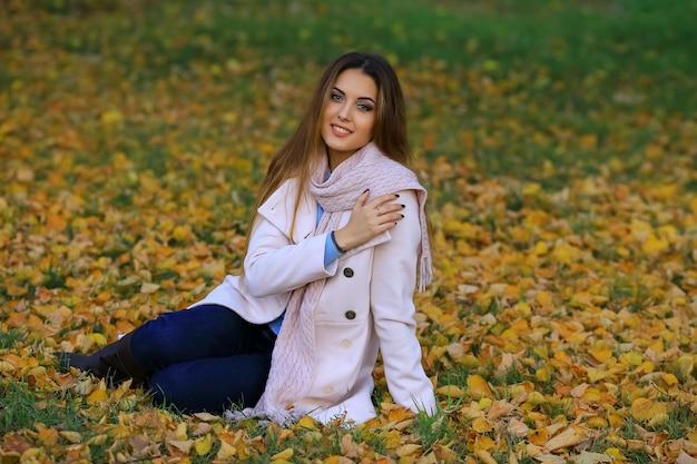 Jonge vrouw die lacht zittend op het gras in de herfst. val gele esdoorn tuin achtergrond.