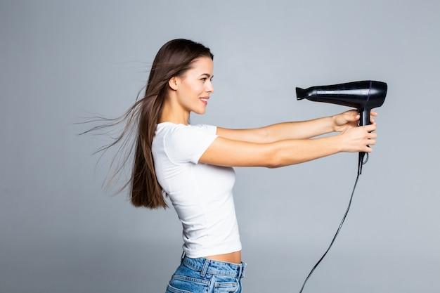 Jonge vrouw die lang haar met elektrische ventilator droogt die op wit wordt geïsoleerd
