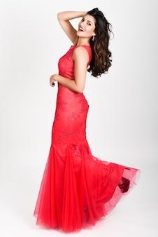 Jonge vrouw die lange rode kleding op witte achtergrond draagt.