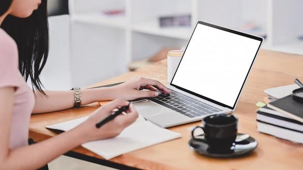 Jonge vrouw die laptop computer met behulp van en op notitieboekjedocument schrijft in bibliotheekruimte.