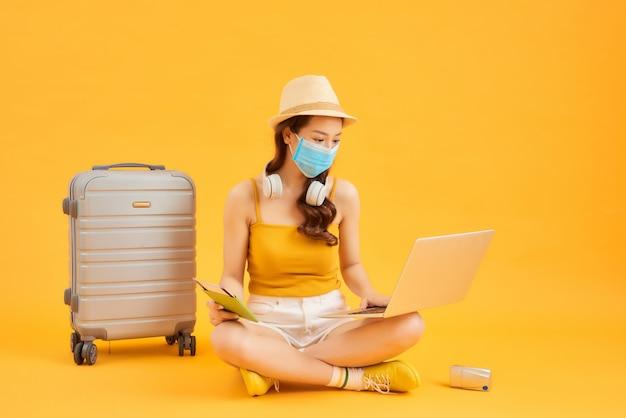 Jonge vrouw die laptop gebruikt, gezichtsmasker draagt tijdens het wachten op de vlucht met haar koffer over oranje achtergrond.