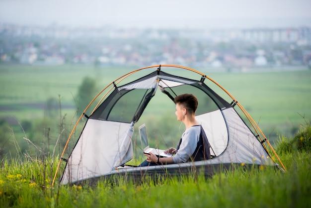 Jonge vrouw die laptop in openlucht met behulp van