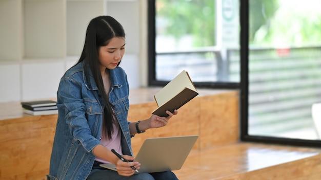 Jonge vrouw die laptop met behulp van en notitieboekjedocument in bibliotheekruimte leest.