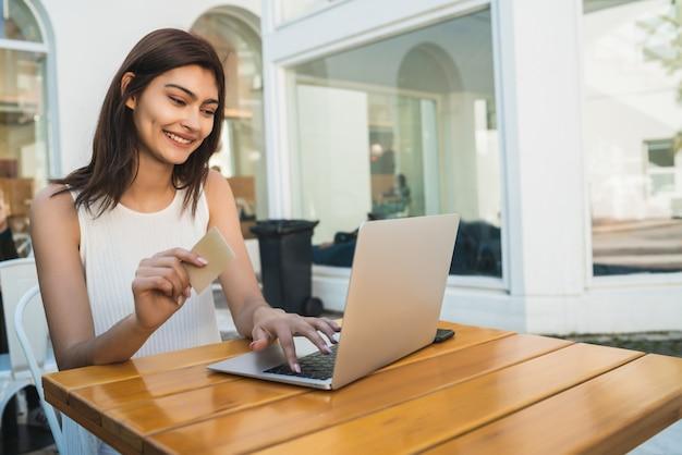 Jonge vrouw die laptop met behulp van om online te winkelen.