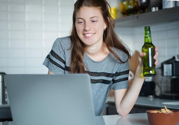Jonge vrouw die laptop met hoofdtelefoons in de keuken met behulp van