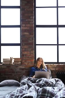 Jonge vrouw die laptop op bed met behulp van