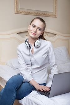 Jonge vrouw die laptop op het bed met behulp van