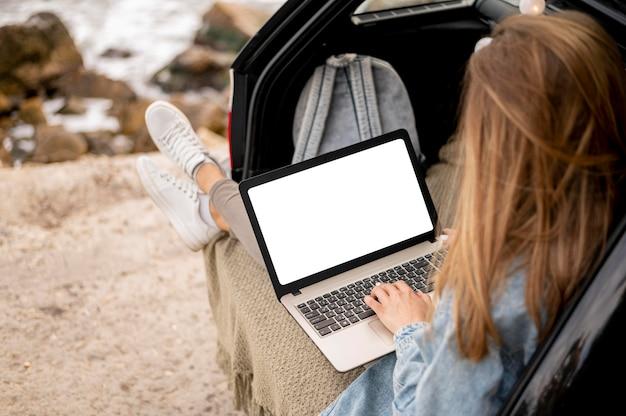 Jonge vrouw die laptop op road trip doorbladert