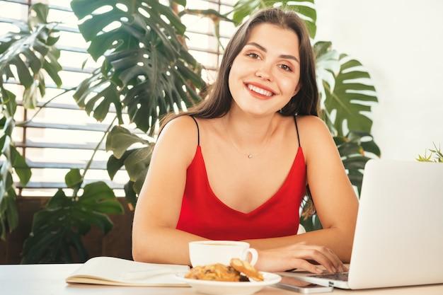 Jonge vrouw die laptop thuis of in koffie met behulp van