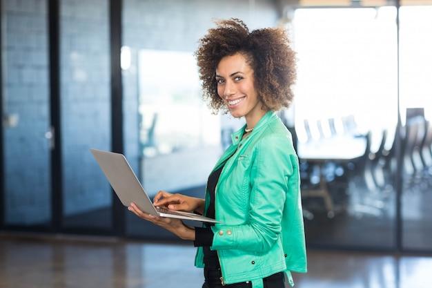 Jonge vrouw die laptop voor conferentieruimte in het bureau met behulp van